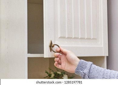 male hand are open the cupboard doors, light wood.