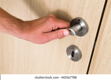 Male hand opening a light wood interior door with a close up view of his hand on the metal handle above a circular keyhole and lock, copy space below