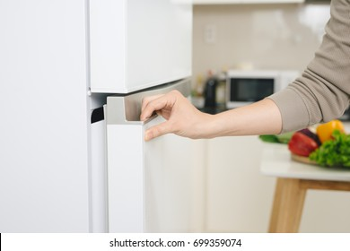 Male hand is opening white refrigerator door