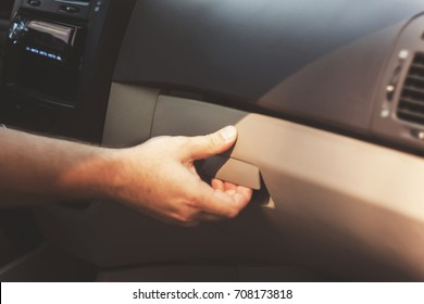 Male hand opens the glove compartment in the car, retro toningÑ?.