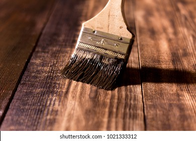 male hand paint wooden surface with brown paint using a paintbrush