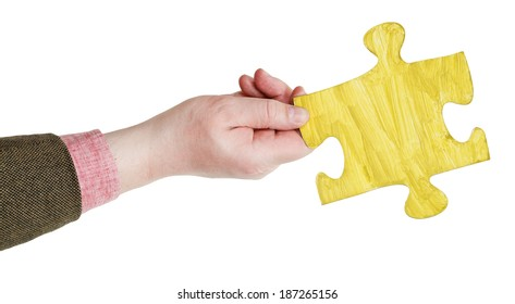 male hand with painted yellow puzzle piece isolated on white background