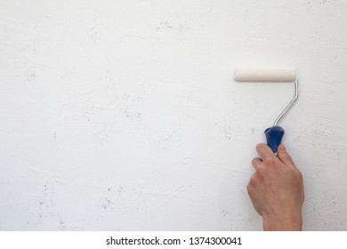 Male hand painting wall with paint roller