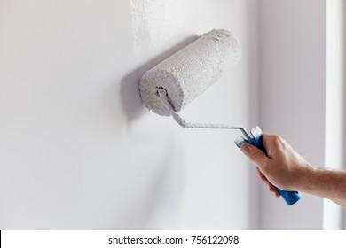 Männliche Malwand mit Malwalze. Malerwohnung, renoviert mit weißer Farbe