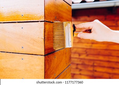 Male hand painting wooden wall with a brush- painting woodwork outside
