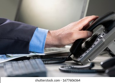 Male hand picking up telephone at an office