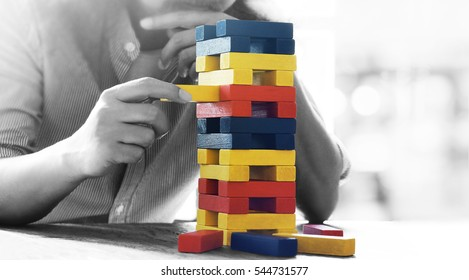 Male hand placed on a tower of wooden blocks on the table concept and strategic planning.