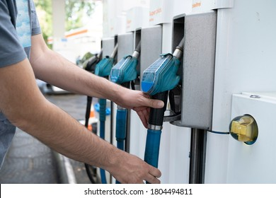 A Male hand places gaspump nozzle back in the pump at the gasstation