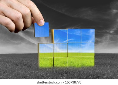Male hand placing last piece of a cube of color grass field. Ecological or positive concept.