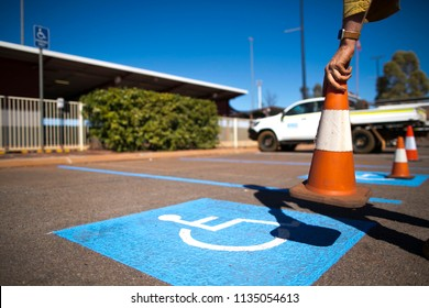 Male hand placing red and white witches hat cone on disable parking sign at Newman Airport, Perth, Australia