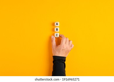 Male hand placing three wooden blocks with the letters of a b and c on yellow background. Business plan decision, choice of alternatives.