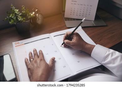 Männliche Hand der Planer schreiben täglich Termin On 2021 Kalender Buch, Arbeitsraum zu Hause. Asiatischer Personalplan und Reiseplan (Urlaubsreise) auf dem Tagebuch am Büroschalter. Zeitplan für das Planerkonzept.