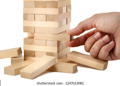 Male hand playing wooden blocks tower game on white background