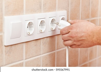 Male hand plugging power cord into electrical socket in the wall - closeup