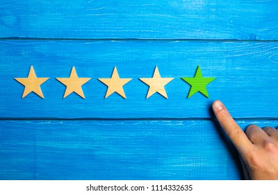 The male hand points to the fifth green star on a blue wooden background. Five Stars. Rating of restaurant or hotel, application. Evaluation of quality and service, critical evaluation.