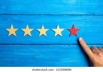 The male hand points to the fifth red star on a blue wooden background. Five Stars. Rating of restaurant or hotel, application. Evaluation of quality and service, critical evaluation.