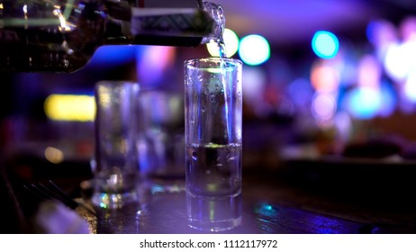 Male hand pouring in huge shot of vodka, alcoholism issues, failed abstinence