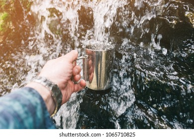 Male hand pouring nature water in cup outdoor.