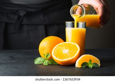 Male hand pouring orange juice into a glass.