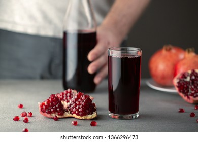Male hand pouring pomegranate juice into a glass.