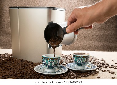 Male hand pouring Turkish coffee.