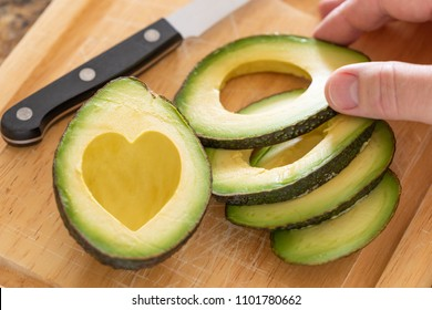 Male Hand Prepares Fresh Cut Avocado With Heart Shaped Pit Area On Wooden Cutting Board.