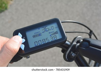 A male hand presses a button on a black electronic bicycle scooter. Bike computer installed on a bicycle's handlebar. Man pressing a button on e-bike control board.