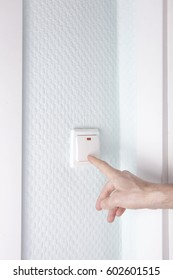 Male hand presses the button of the switch. Turns on (off) the light