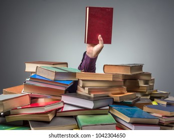 Male hand protruding from pile of books holding the book he was looking for