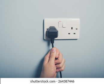 A male hand is pulling an electrical cord plugged into a wall socket
