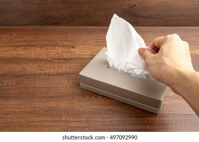 Male hand pulling white facial tissue from a box.