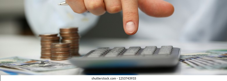 Male hand push key silver calculator is lying on desk cash dollar plots in home office setting. Calculation of family expenses social income population freelance irs situation growth research concept