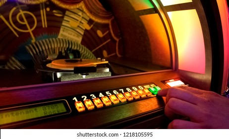 Male hand pushing buttons to play song on old musical box, selecting records