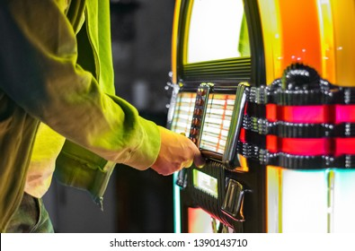 Male hand pushing buttons to play song on old Jukebox, selecting records