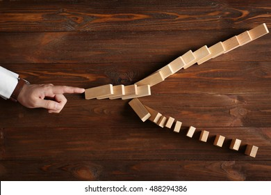 Male hand pushing dominoes on wooden table