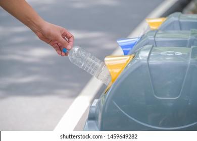 Male hand put used bottle in recycle bin