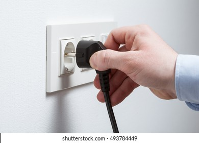 Male hand puts plug in the socket, closeup shot
