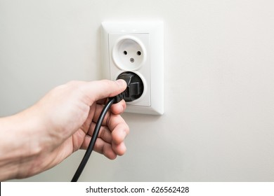 Male hand puts plug in the socket
