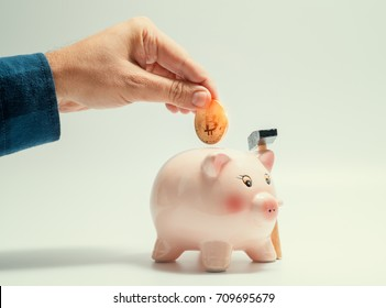 male hand putting bitcoin in to piggy bank. cryptocurrency investment concept
