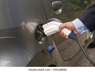 Male hand putting charger into an electric car.  Wearing shirt and suit.