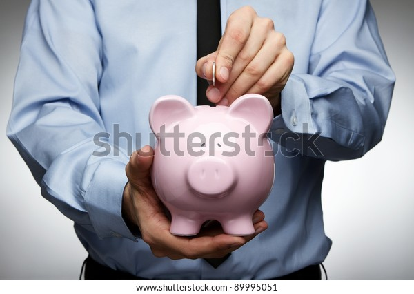 Male hand putting coin into a piggy bank