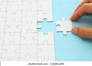 male hand putting the last piece in the puzzle