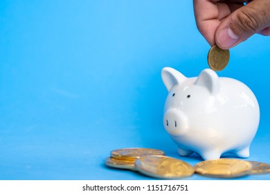 Male hand putting money coins in white ceramic piggy bank on light blue pastel color background standing over pile of coins for fund finance scholarship saving and education concept.