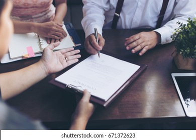 male hand putting signature, running own small business, have a contract in place to protect it, basics of writing contract, one sentence in a contract can cost a business