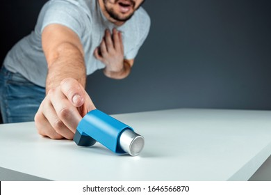 The male hand reaches for an asthma inhaler, an asthmatic attack. The concept of treatment of bronchial asthma, cough, allergies, dyspnea