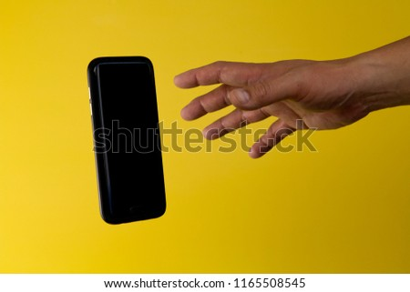 A male hand reaching out to grab a floating smartphone, against a yellow background.