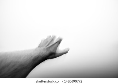 Male Hand Reaching Out into a Thick ominous Fog where fingers Disappear. Moody Black and White with Dark to Light Gradient