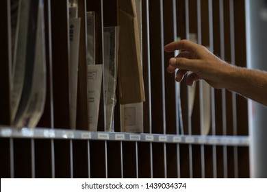 Male hand reaching for sorted post or mail in pigeon holes in a postal depot in a corporate business