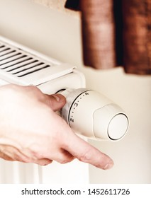 Male hand reducing heating in home for saving money. Radiator Thermostat.