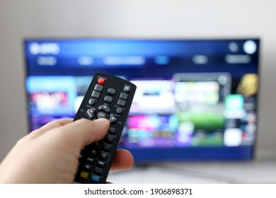 Male hand with remote controller on smart TV screen background. Person choosing streaming services, watching movies - Shutterstock ID 1906898371